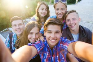 Youth gathered together smiling for selfie