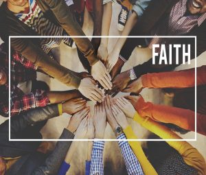"""Many hands reaching into centre with phot taken from above, with the word """"Faith"""" over the top."""