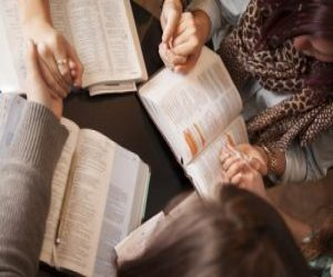 Image of hands being held over open Bibles during prayer.