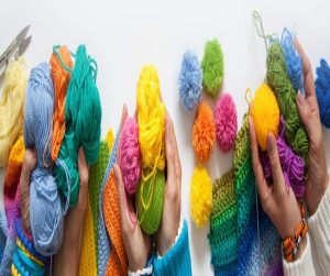 3 pairs of hands holding balls of multi coloured wool.