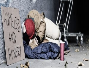 "Man sleeping rough on pavement against wall with sign reading ""Homeless and Hungry"""